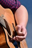 Handen av den kvinnliga gitarristklockas slag stränger på den akustiska gitarren med hackan Royaltyfri Fotografi