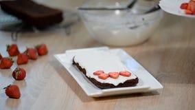 Handen av den kvinnliga konditor gör en läcker jordgubbe att baka ihop Matlagningefterrätt i köket stock video