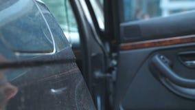Handen av den manliga affärsmannen öppnar och rymmer bildörren för den härliga unga kvinnan Manöppningsdörr av bilen för arkivfilmer