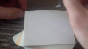 Handen av den unga mannen drar en ledsen framsida, då korsat ut, river av sidan och drar en smileyframsida arkivfilmer