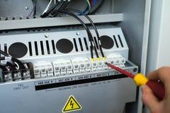 Handen av elektrikeren med skruvmejsel drar åt upp elektriska terminaler Arkivbilder