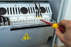 Handen av elektrikeren med skruvmejsel drar åt upp elektriska terminaler av transformatorn Arkivfoton