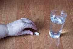 Handen av en äldre kvinna tar en preventivpiller, ett exponeringsglas av vatten, en närbildpreventivpiller royaltyfria bilder