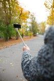 Handen av en äldre man som rymmer en monopod med en mobiltelefon royaltyfri bild