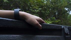 Handen av en asiatisk grabb som knackar lätt på för takten av sången lyssnar han, i skogen som förnyar sig lager videofilmer