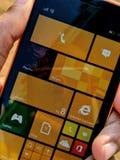 Handen av en grabb som rymmer f?nster, ringer av Nokia royaltyfri foto