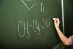 Handen av en kemilärare skriver på svart tavla royaltyfria bilder