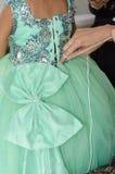 Handen av en kvinna som binder bandet på gröna frodiga flickor, klär Royaltyfri Bild