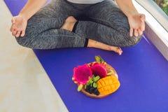 Handen av en kvinna som mediterar i en yoga, poserar och att sitta i lotusblomma med frukter som är främsta av hennes drakefrukt, Royaltyfria Bilder