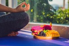 Handen av en kvinna som mediterar i en yoga, poserar och att sitta i lotusblomma med frukter som är främsta av hennes drakefrukt, Arkivfoto