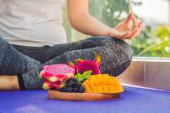 Handen av en kvinna som mediterar i en yoga, poserar och att sitta i lotusblomma med frukter som är främsta av hennes drakefrukt, Arkivbild