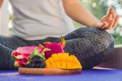 Handen av en kvinna som mediterar i en yoga, poserar och att sitta i lotusblomma med frukter som är främsta av hennes drakefrukt, Royaltyfria Foton