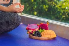 Handen av en kvinna som mediterar i en yoga, poserar och att sitta i lotusblomma med frukter som är främsta av hennes drakefrukt, Royaltyfri Foto