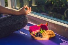 Handen av en kvinna som mediterar i en yoga, poserar och att sitta i lotusblomma med frukter som är främsta av hennes drakefrukt, Royaltyfri Bild
