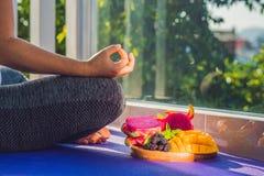 Handen av en kvinna som mediterar i en yoga, poserar och att sitta i lotusblomma med frukter som är främsta av hennes drakefrukt, Royaltyfri Fotografi