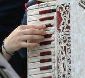 Handen av en kvinna spelar det forntida dragspels- tangentbordet royaltyfria bilder