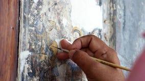 Handen av en målningkonstnär reparerar en kinesisk målning Renovering av kinesisk målning på väggarna av gamla byggnader arkivfilmer