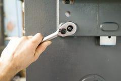 Handen av en man rymmer hålighetskiftnyckeln royaltyfri foto