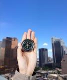 Handen av en man som rymmer en magnetisk kompass över byggnader för en stad Royaltyfri Bild
