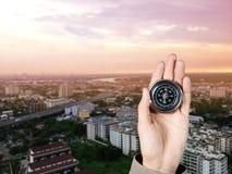 Handen av en man som rymmer en magnetisk kompass över byggnader för en stad Arkivbild