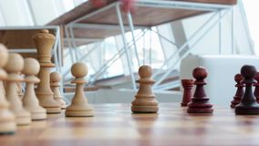 Handen av en ung flicka gör en flyttning med ett schackstycke ovanför schackbrädet i rummet Spela schack, brädelekar HD stock video