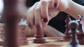 Handen av en ung flicka gör en flyttning med ett schackstycke ovanför schackbrädet i rummet Spela schack, brädelekar HD lager videofilmer