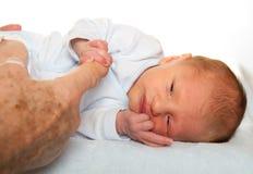 Handen av ett nyfött behandla som ett barn Arkivbild