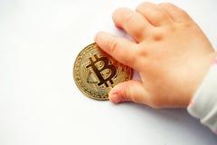 Handen av ett småbarn når för ett bitcoinmynt royaltyfria foton