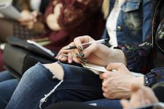Handen av flickan med en penna och notepadlögner på hennes knänärbild royaltyfria foton