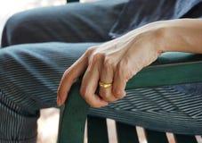 Handen av gifta kvinnor som sitter på en stol royaltyfria foton