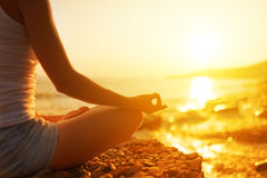 Handen av kvinnan som mediterar i en yoga, poserar på stranden