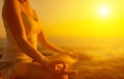 Handen av kvinnan som mediterar i yoga, poserar på stranden