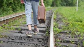 Handen av mannen med resväskan som går på järnvägsspår arkivfilmer