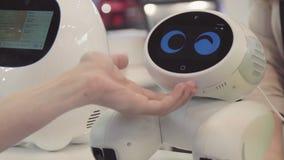 Handen av mannen trycker på roboten Roboten är lycklig med handlaget av en människa begrepp isolerad teknologiwhite arkivbild