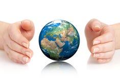 Handen av personen rymmer jordklotet. Royaltyfri Bild