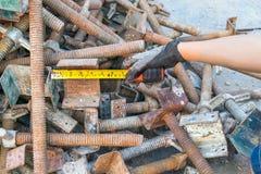 Handen bearbetar att mäta bandet med stålbultar, muttrar, skruvmaterial till byggnadsställningpol Arkivbilder