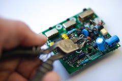 Handen biter av radiobeståndsdelarna på det elektroniska brädet med klippplattången, närbild arkivfoton