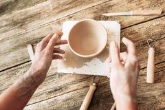 Handen boven kleikom op houten lijst, artisanaal POV stock foto