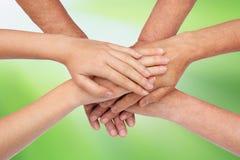 Handen bovenop groen elkaar stock afbeeldingen