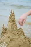 Handen bygger en sandslott Royaltyfri Bild