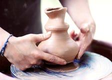 Handen die aan aardewerkwiel werken Stock Afbeelding