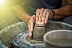 Handen die aan aardewerkwiel werken Stock Fotografie