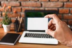 Handen die adreskaartje met het werk ruimte houden bij de achtergrond royalty-vrije stock foto