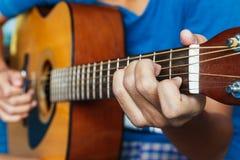 Handen die akoestische gitaar spelen stock afbeelding