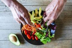 Handen die avocadosalade en plaat van nac eten Stock Foto
