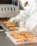 Handen die bij een hamburgermachine werken Royalty-vrije Stock Foto