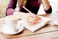 Handen die bij notitieboekje in koffie schrijven royalty-vrije stock fotografie