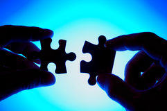 Handen die bij twee raadselstukken aansluiten zich. Royalty-vrije Stock Afbeelding