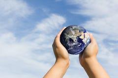 Handen die blauwe aarde houden Elementen van dit die beeld door Na wordt geleverd Stock Afbeeldingen
