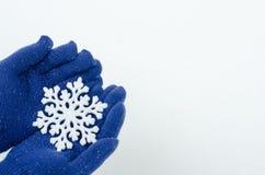 Handen die blauwe handschoenen dragen die een grote sneeuwvlok houden Royalty-vrije Stock Foto's